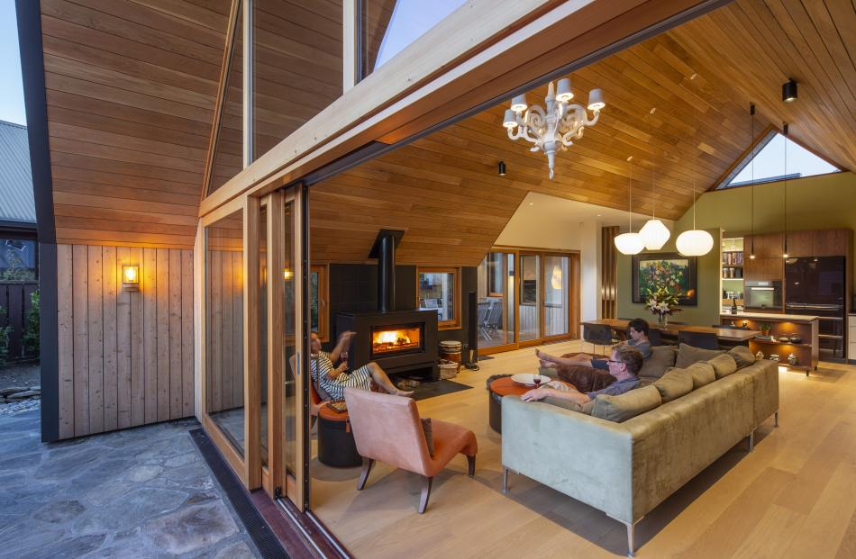 The living area features a tongue and groove ceiling and opens on to a schist 