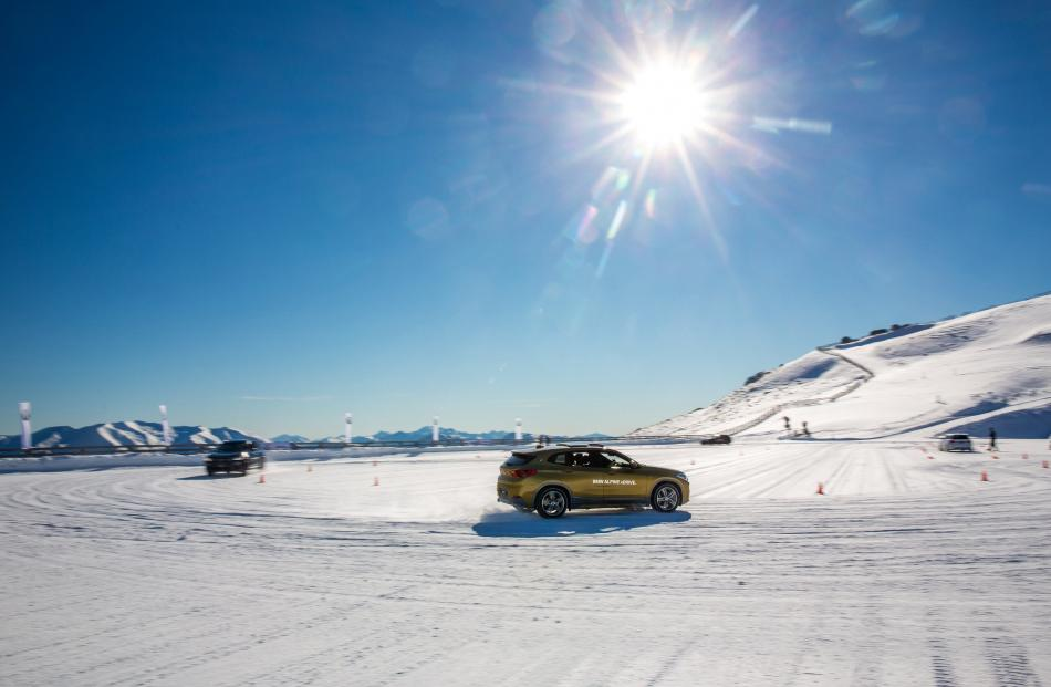 Tackling the snow slalom course in four-wheel-drive BMWs.