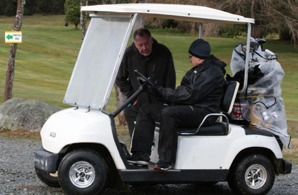 Glen Donovan, manager of Fiordland Hotel (in cart), discusses the score sheet with his golf...