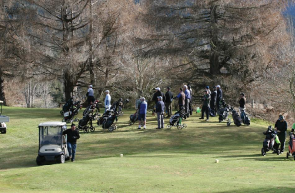 Sunday, weather improved and sun out. Bottleneck of teams waiting to play off one of the holes...