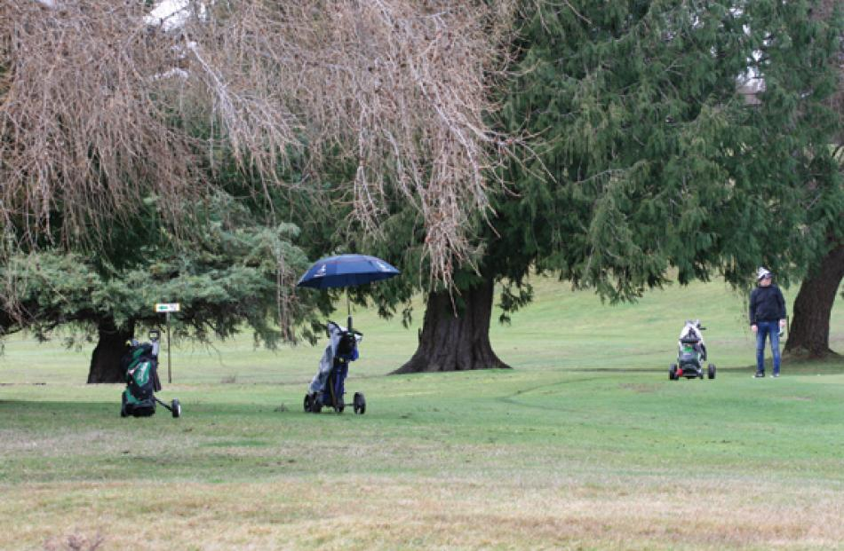 Golfers played on Saturday in wet, windy, cold conditions, where umbrellas were well used to...