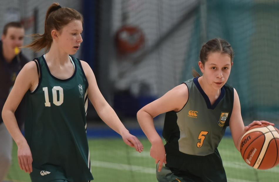 Bayfield High School player Veronika Luthar dribbles the ball down the court with St Hilda's Collegiate player Tamzin Burgess in pursuit. Photos: Gregor Richardson