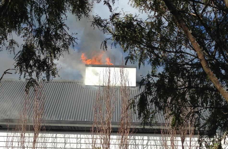 Flames spurt from the roof.