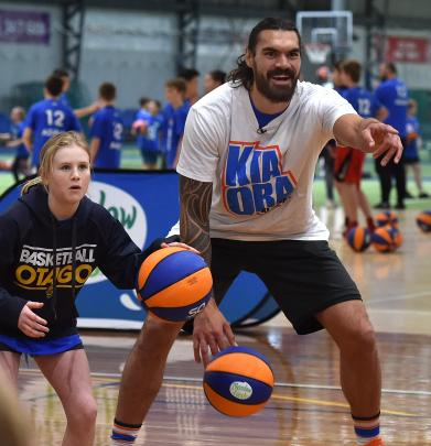 Columba College's Amelia Loudon (11) dribbles the ball next to Steven Adams at yesterday's camp at the Edgar Centre. Photos: Peter McIntosh