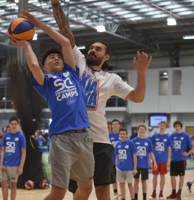 Waitaki Boys' High School pupil Danyon Ashcroft (14) takes the ball to the hoop against Steven Adams at yesterday's camp at the Edgar Centre.