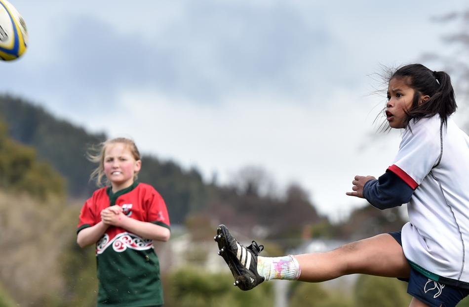 Jamaica Cabantoc (13), of Kavanagh College, kicks the ball, as Abby Cockill (11) of Kaikorai Valley College looks on.