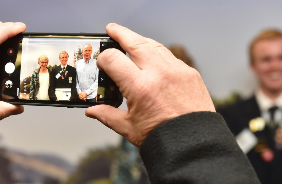 Roxburgh Area School principal Gary Pasco takes a photo of his pupil Alex Darling and his parents...