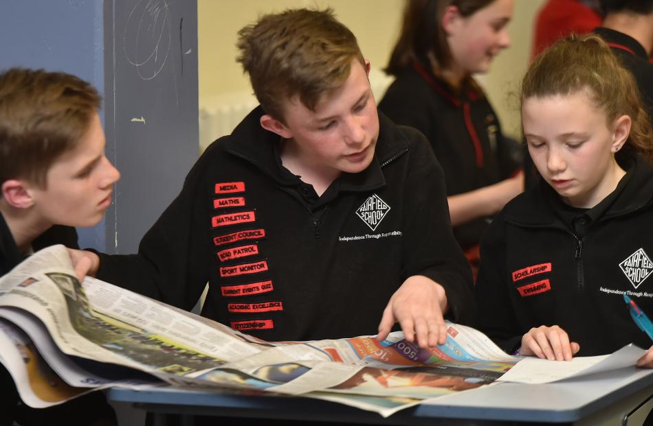 Ted McFadgen (12), Ben Turnbull (13) and Georgia Te Raki (11), from Fairfield School, scour the Otago Daily Times for last night's Extra! current events quiz.