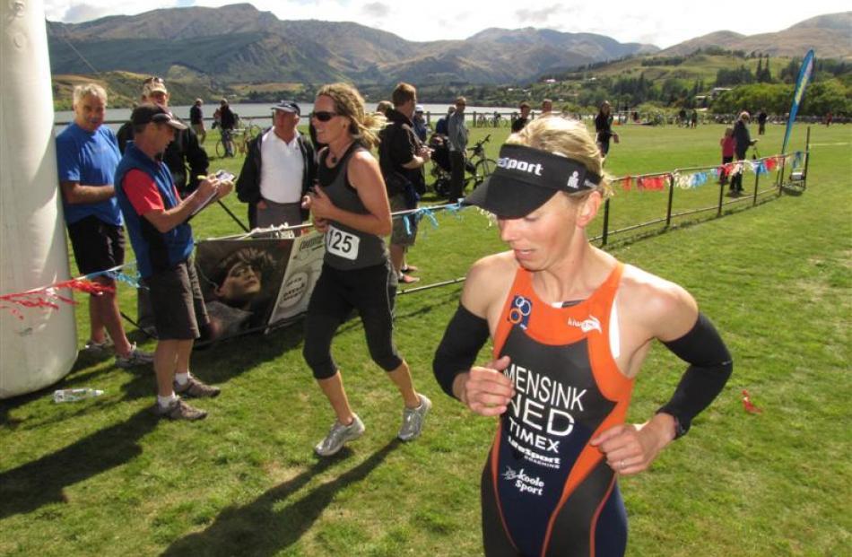 Christina Spence (No 125), of Hamilton, crosses the finish line, alongside 2008 Olympian Lisa...