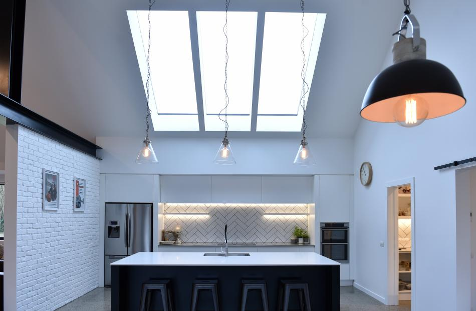 The window above the kitchen looks like three separate skylights but is one large piece of glass...