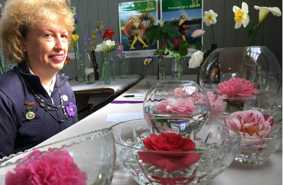 Lowcliffe WI member Susan Philpott looks at the ``floating Camellia in glass container'' entries.