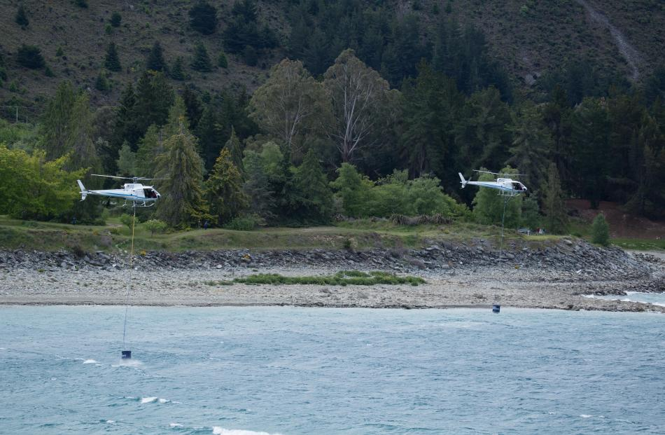 Helicopters fill up monsoon buckets to fight the blaze at Lake Hawea. Photo: Andy Cole