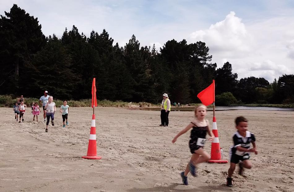 The children running at high speed in the 2km beach run.