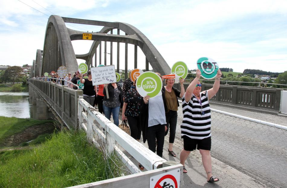 80 primary teachers and principals marched across the Balclutha Bridge as they supported the...