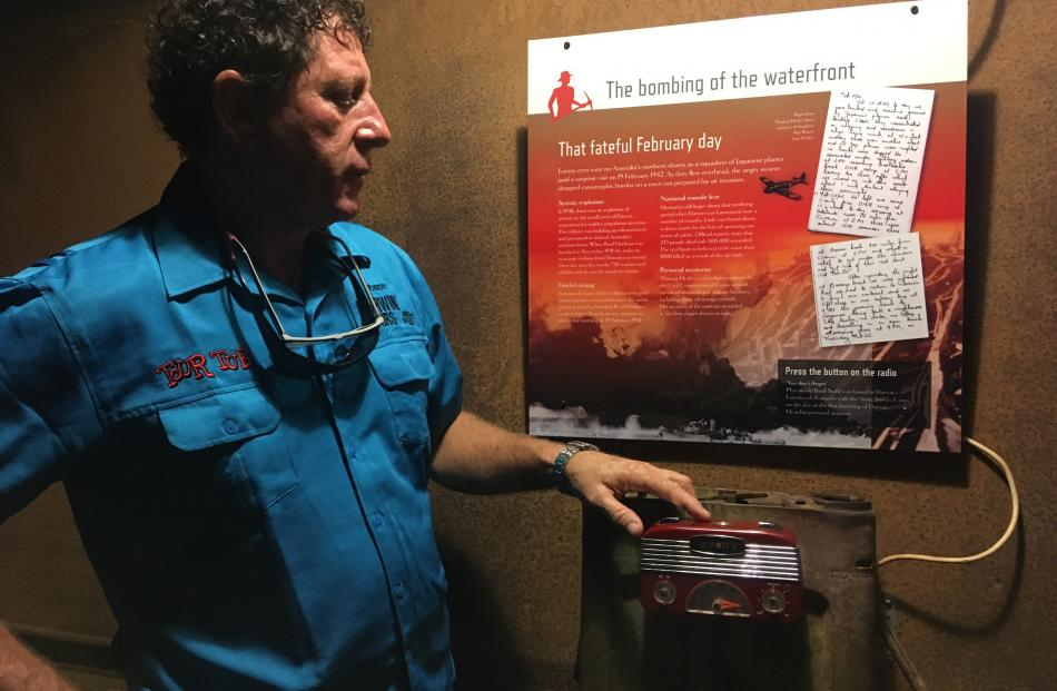 Darwin Tours owner Rob Marchant shows one of the interpretative panels in Darwin's World War 2...