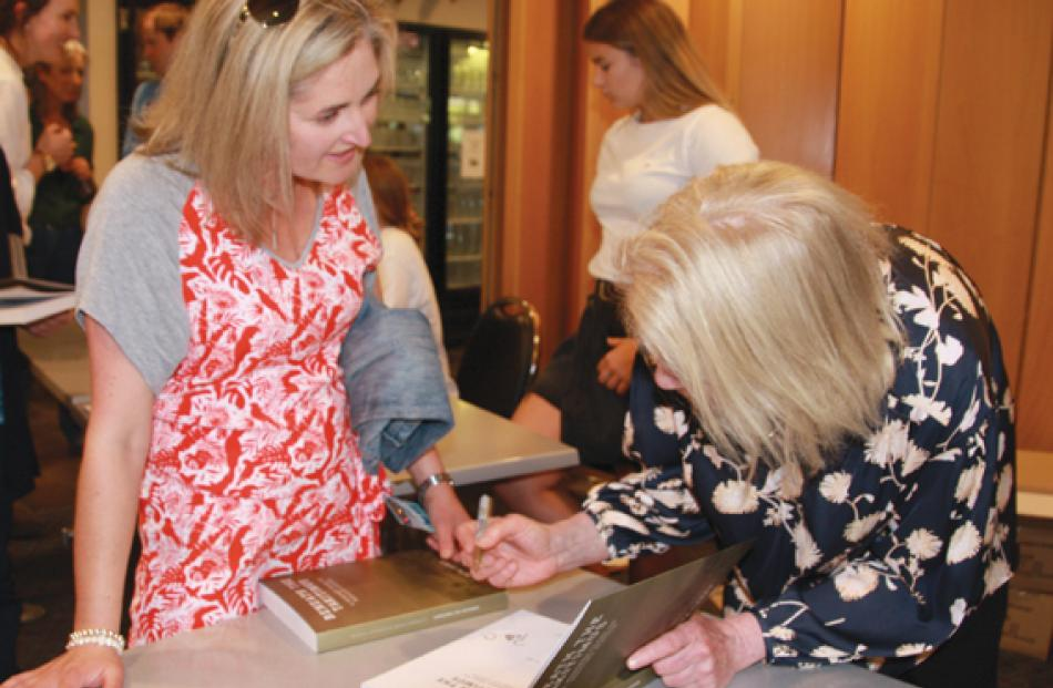 """Bridget Speight, researcher for the book """"Beneath the Takitimus"""", signing the book  for Moretta..."""