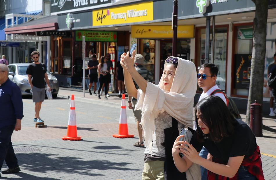 Two tourists captures the moment on Rees St, Queenstown. PHOTO: PAUL TAYLOR