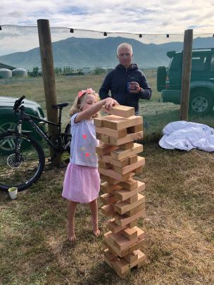 Billy Collins (6) carefully places her block in a game of Giant Jenga while Grandad (Tony...