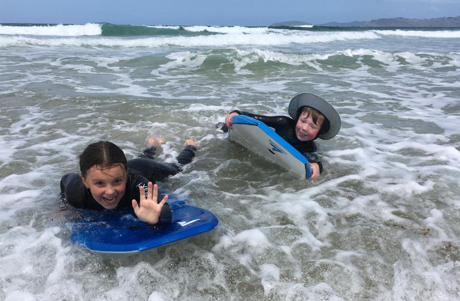 Cousins Isla and Adam Ludgate (both 9) in the surf at Karitane on Boxing Day. Photo: Jackie Ludgate