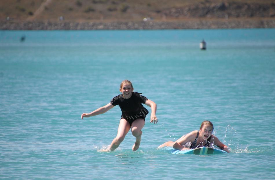 Kate Merriman (11) leaps off the paddle board, much to the relief of her sister, Islay  (13), on...