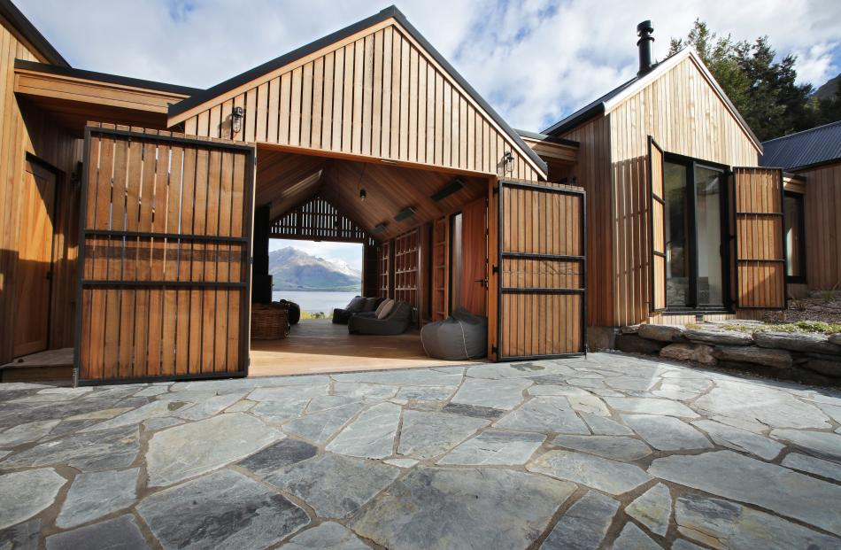 The outdoor room can be opened to the lake in front and to a schist courtyard at the rear.