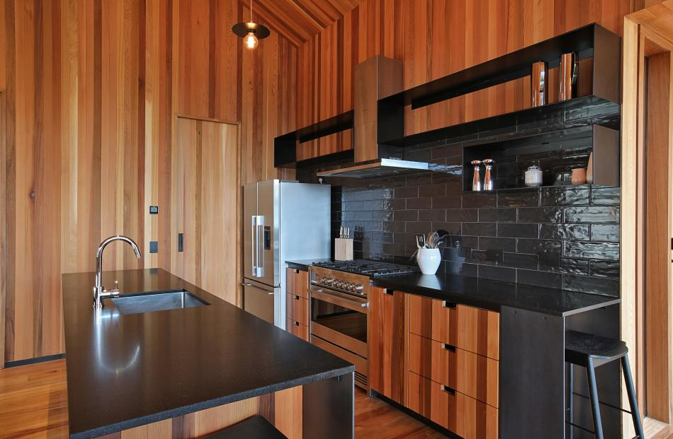 The kitchen has a honed Bengal black stone island and bench-top, band-sawn cedar joinery, glossy...