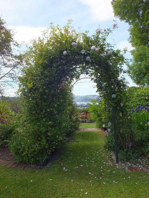 A rose arch frames a harbour view.
