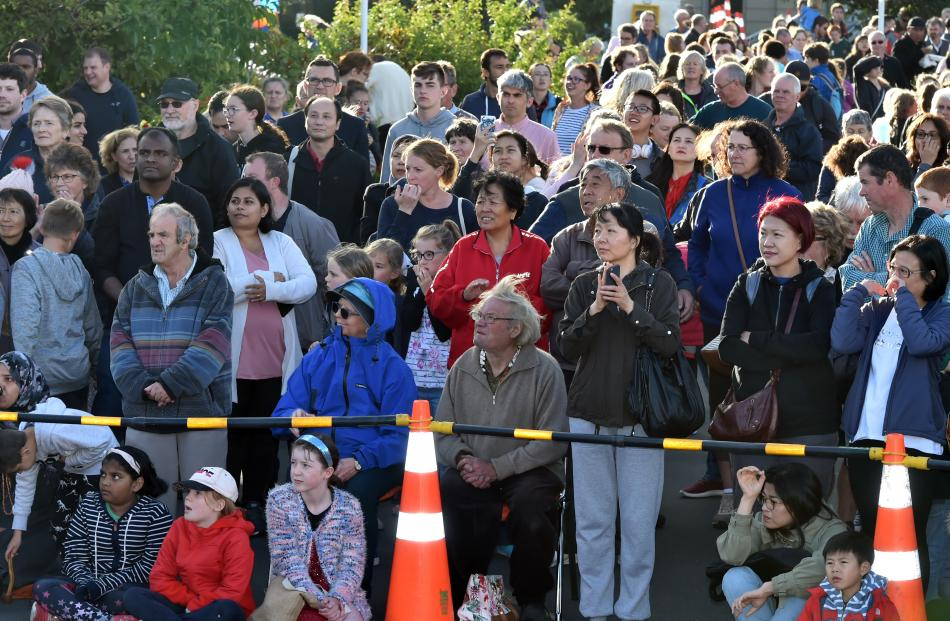 Some of the large crowd at the Dunedin Chinese Garden watch the vivid spectacle.