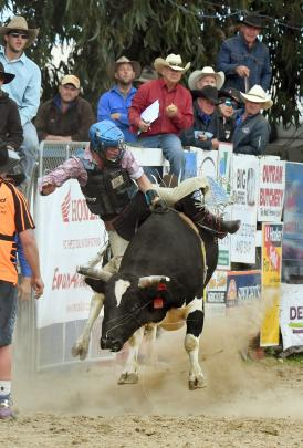Sam Church competes in the open bull ride at the Outram Rodeo, despite a severely injured foot.