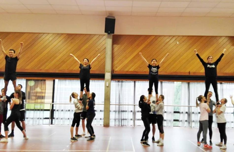 No experience necessary: advanced cheerleaders and novice athletes stunt together at University...