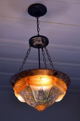 The owners have replaced all the home's paper shades with old light fixtures. This one has women...