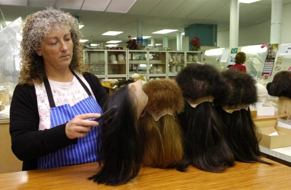 Lynda Dockerty brushes a partly-completed wig.