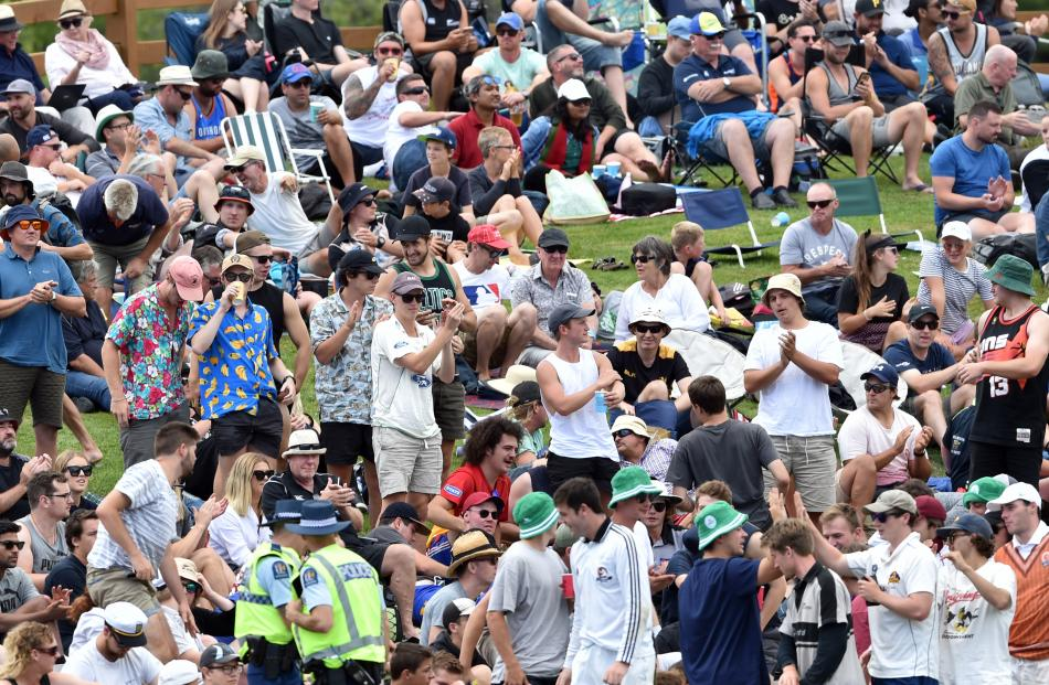 Cricket fans and tertiary students celebrating Orientation Week sat side by side on the banks of...
