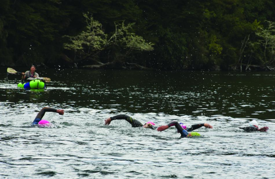 "Swimmers navigating the Upper Waiau River during the ""fast"" swim, with all swimmers having..."