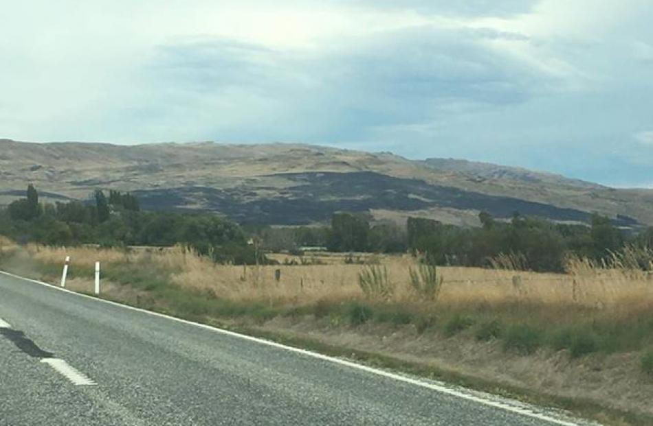 A dark patch on the hills shows where the fire raged overnight. Photo: George Block
