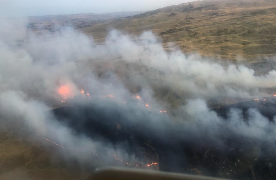 Winds fan smoke as the hillside burns. Photo: Supplied