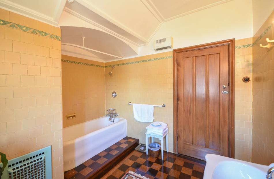 This bathroom, one of three in the house, still has its original bath and yellow tiles.