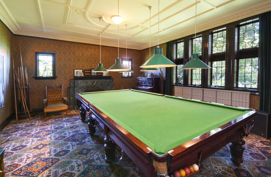 The full-size billiards table and carved cue stand were bought with the house.
