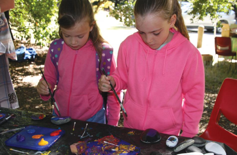 7岁的诺瓦和她的妹妹9岁的蒂娜娜的布雷纳猎人在儿童画画岩石...