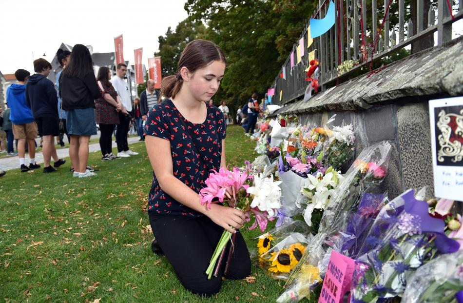 Eloise Piper lays flowers at a makeshift memorial near the Arts Centre on Saturday afternoon.
