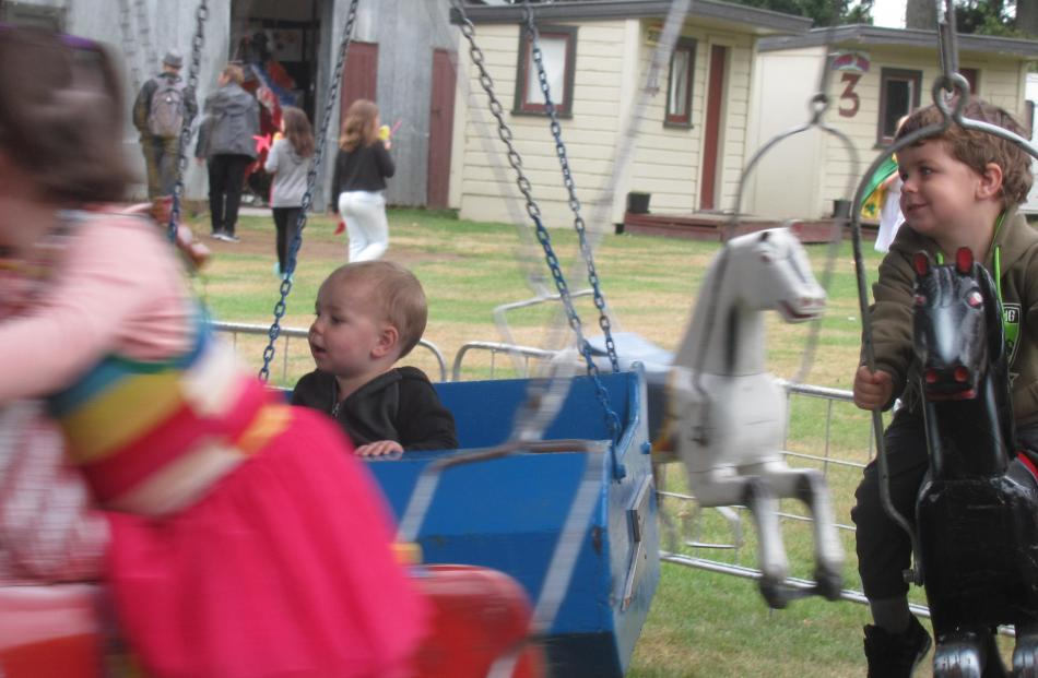Siblings Fletcher (17 months) and Archer Stone (3), of Dorie, enjoy a ride on the merry-go-round.