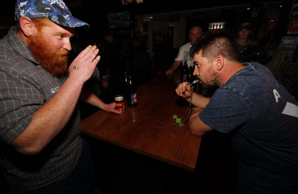 John Hunter, of Wyndham, shows Nathan Smith, of Invercargill, how to make a duck call.
