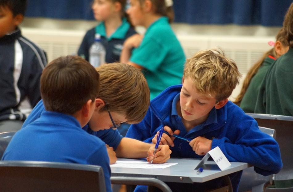 Fenwick School pupil James Soal (10, right) looks over his team's answers alongside Carter...