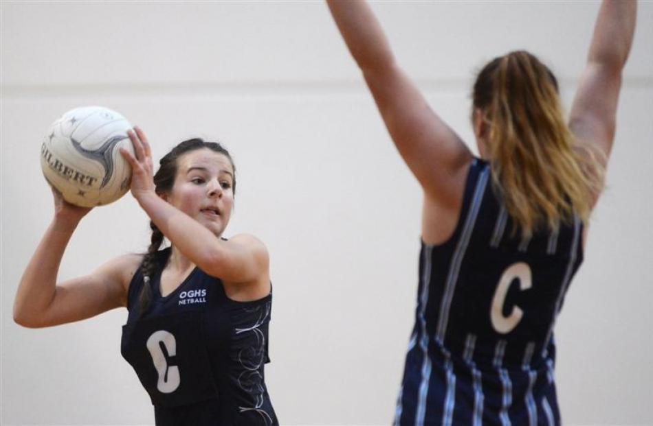 Caitlin Thomson (14), of Otago Girls' High School, looks to lob the ball past Arnika Buchan (14),...