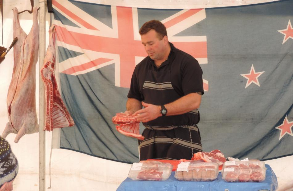 Whitestone Meats butcher Jeff Wright demonstrates how different cuts of lamb are created. He...