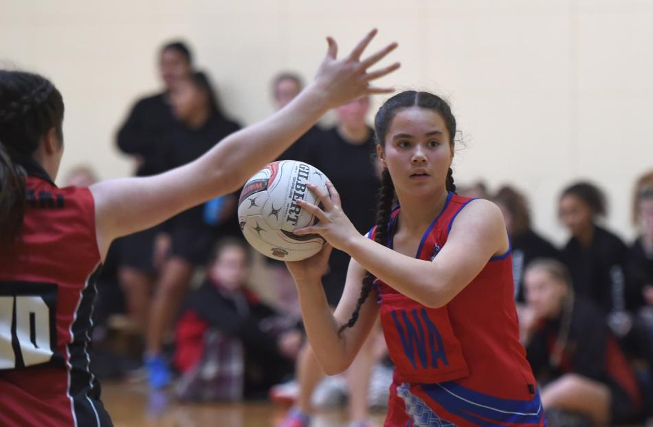 Queen's High School wing attack Monique Wiparata (14) looks to pass the ball.