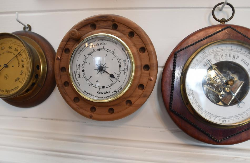 A brass hygrometer and a barometer flank a tide clock in the shape of a fly fishing reel that Mrs...