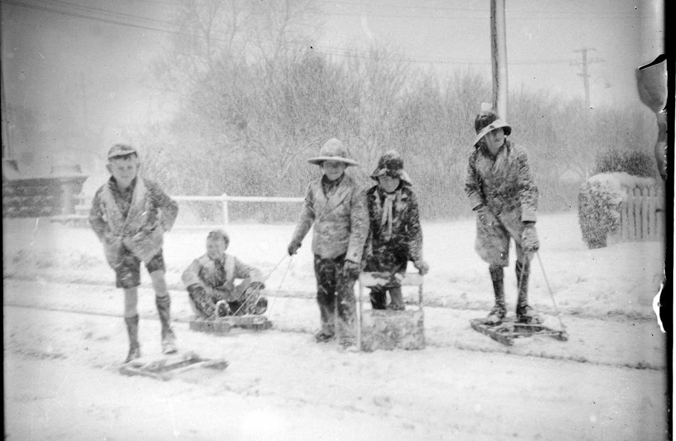 Children, some in shorts, play in the snow near the bridge at the north end of George St. PHOTO:...