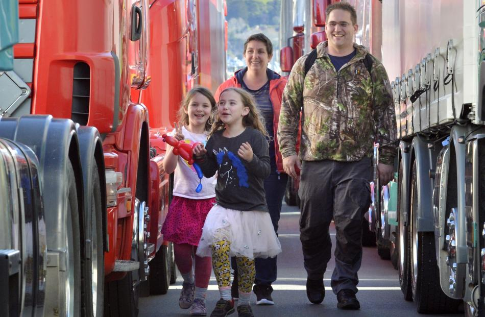 Adele Elmiger and John Laughton walk through the rows of trucks with their daughters Hazel  (6,...