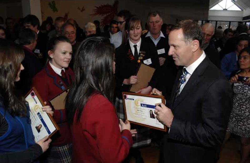 Prime Minister John Key signs her certificate for Kylie Price of Kavanagh College.